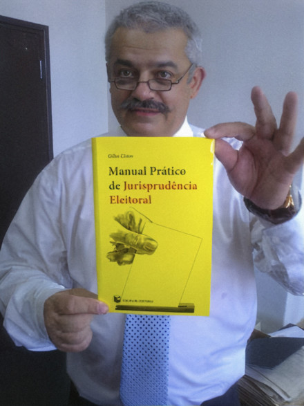 Gilles Cistac, who was a constitutional lawyer, holding the book he published on electoral law in Mozambique