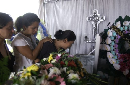 Relatives mourn over Olivas's coffin